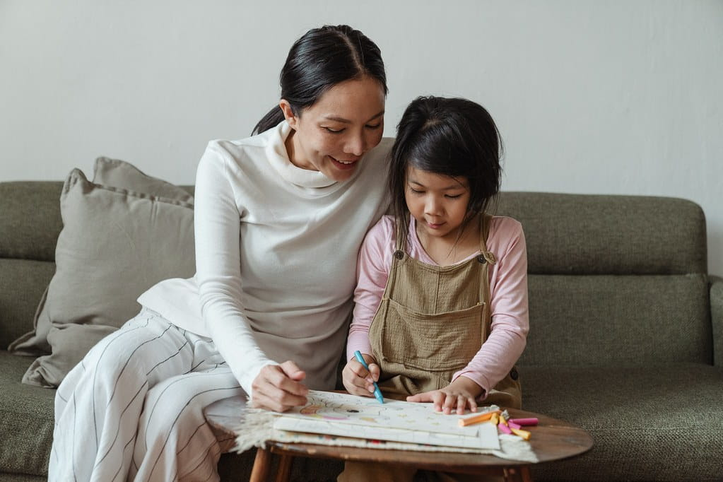 Mum and daughter sat on the sofa together drawing.