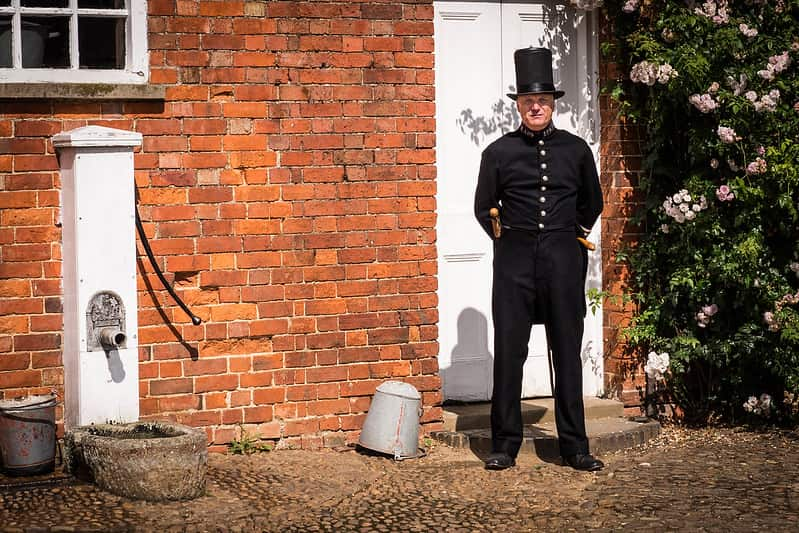 A Victorian policeman standing outside a house in his uniform.