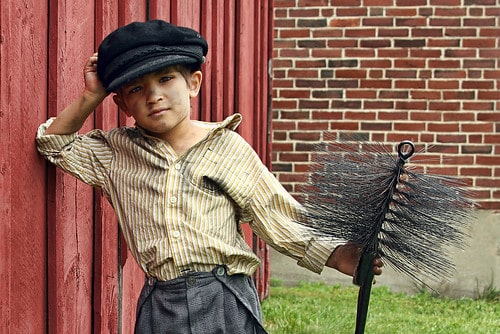 Victorian chimney sweep boy with soot on his clothes.