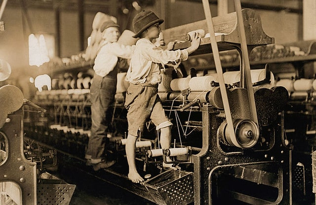 Two young boys working in the weaving factory.