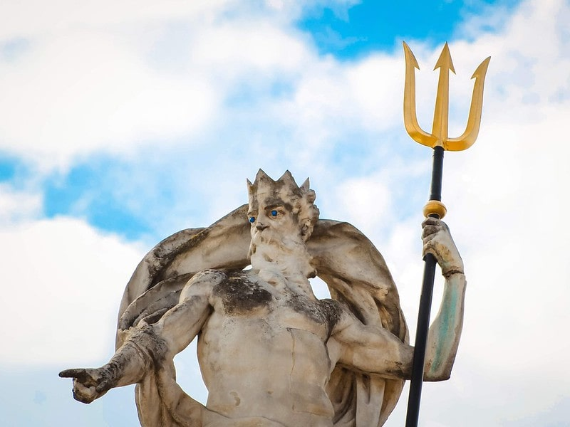 Statue of Neptune holding a golden trident in his hand.