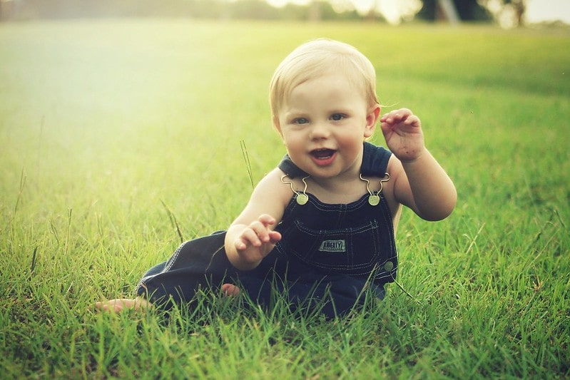 Blonde baby wearing dungarees sat in the grass smiling.