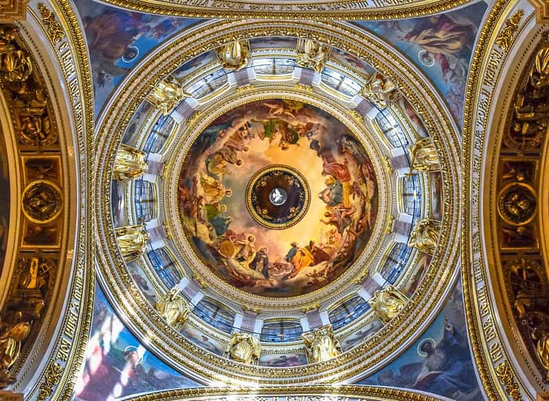 Beautiful painted ceiling of a church dome with gold borders around the arches.