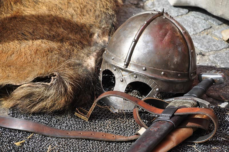 A mediaeval helmet, sword and armour lying on the stone floor.