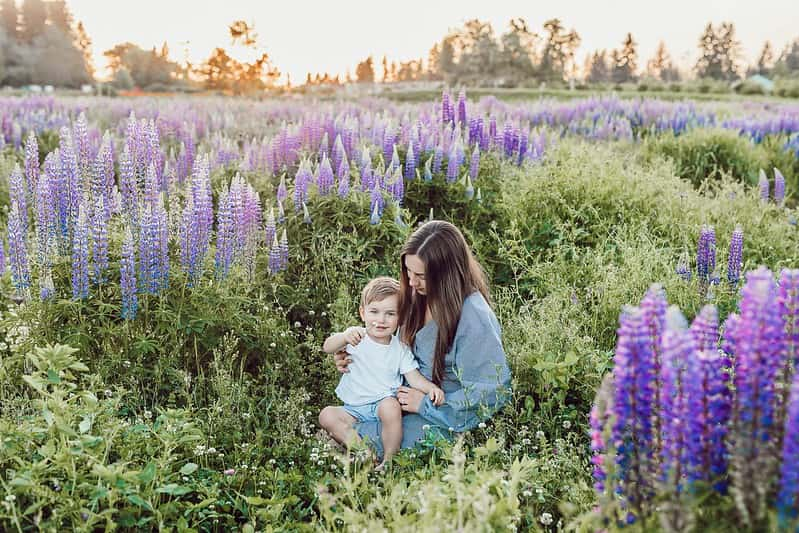 Mum sitting with her baby son on her lap in a field of purple flowers.