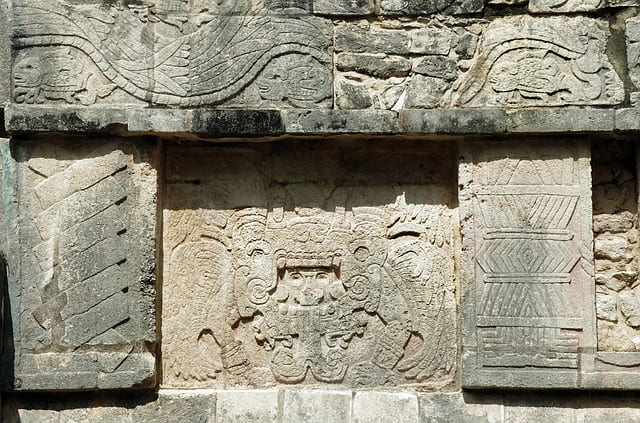 Engravings of god figures in the stone walls of Mayan structures.