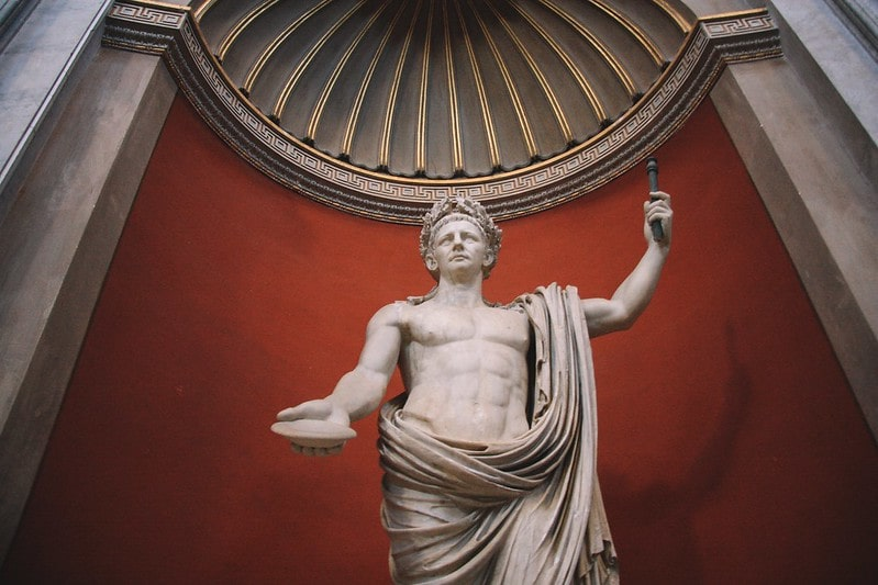 Statue of Julius Caesar on a podium in front of a red painted wall in a museum.