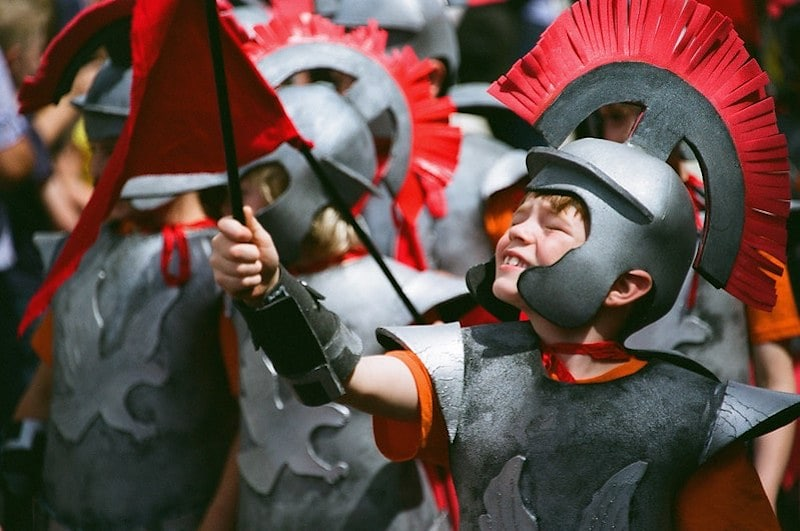 Young boys dressed up as Roman soldiers preparing to go into battle.