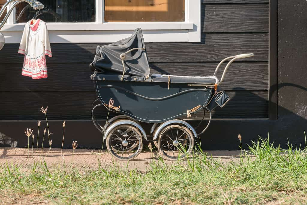 Old-fashioned Victorian stroller left outside a house.