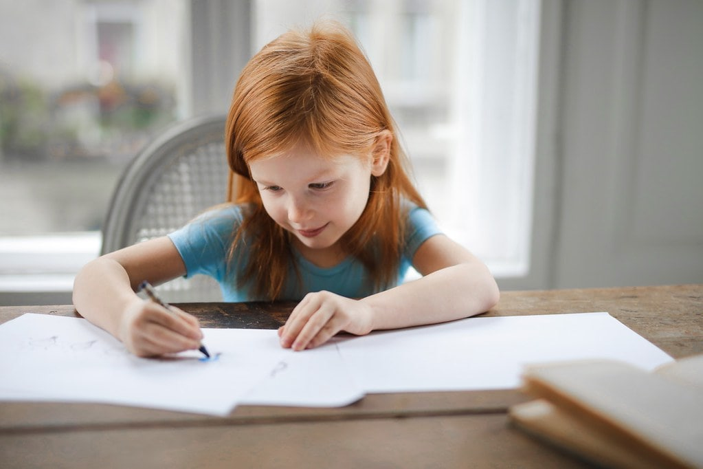 Young girl sat at the table drawing on some pieces of paper.