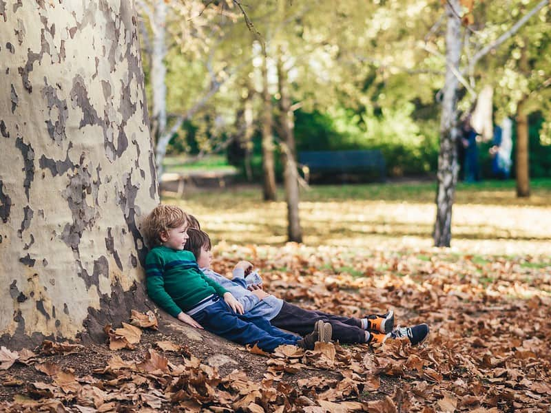 Little boys sat relaxing against a tree, enjoying being outdoors in nature.