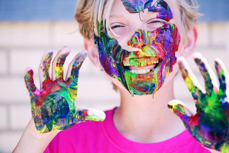 Kid smiling with colourful paint all over their hands, face and teeth.