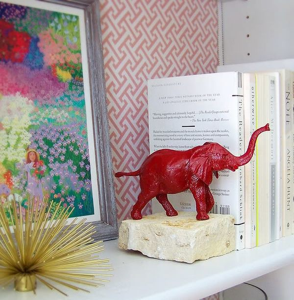 Bookend with a red elephant with its trunk in the air on it.