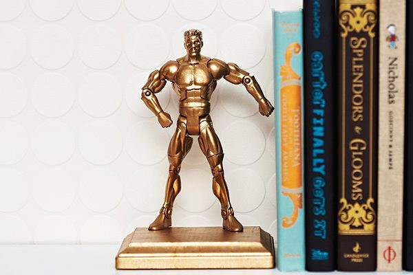 A gold man action figure as a bookend.