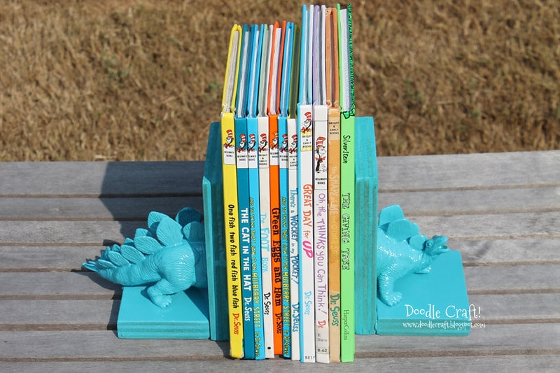 Bookends made with half of a blue toy dinosaur on each side of the books.