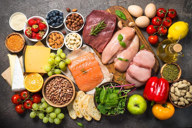 A variety of all kinds of food on a chopping board, including meat, fish, cheese, nuts, eggs, vegetables and oils.