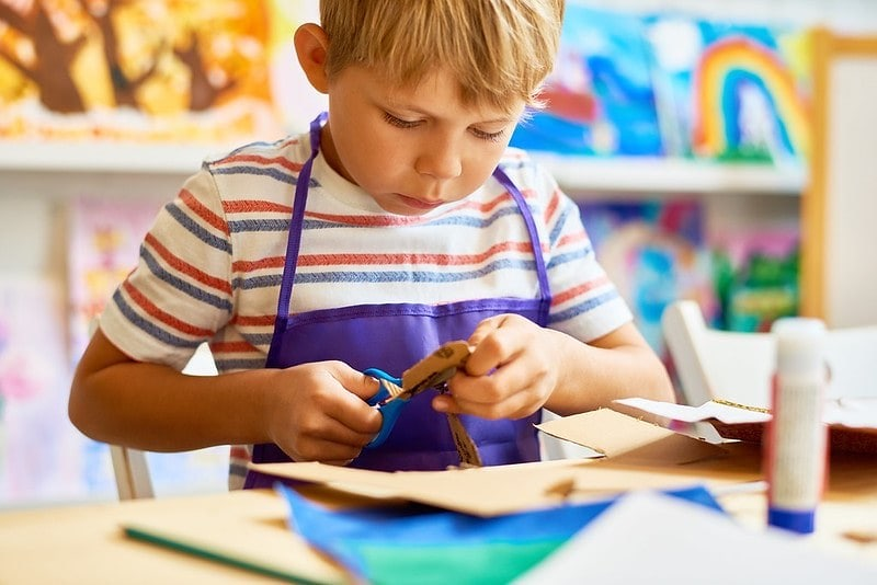 Young boy wearing an apron sat at the table cutting out cardboard.