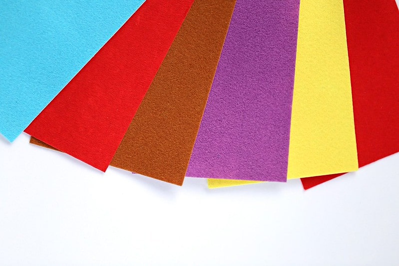 Different colours of felt paper fanned out.