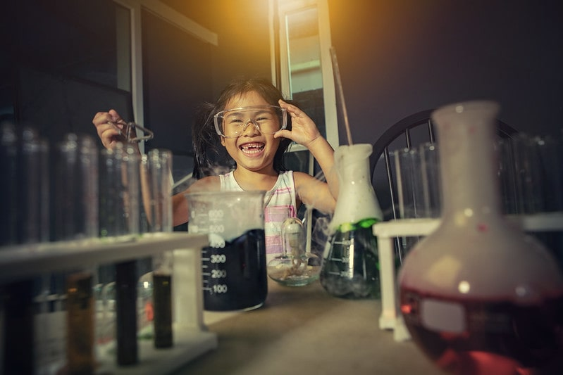 Little girl wearing goggles, laughing while doing a chemistry experiment.