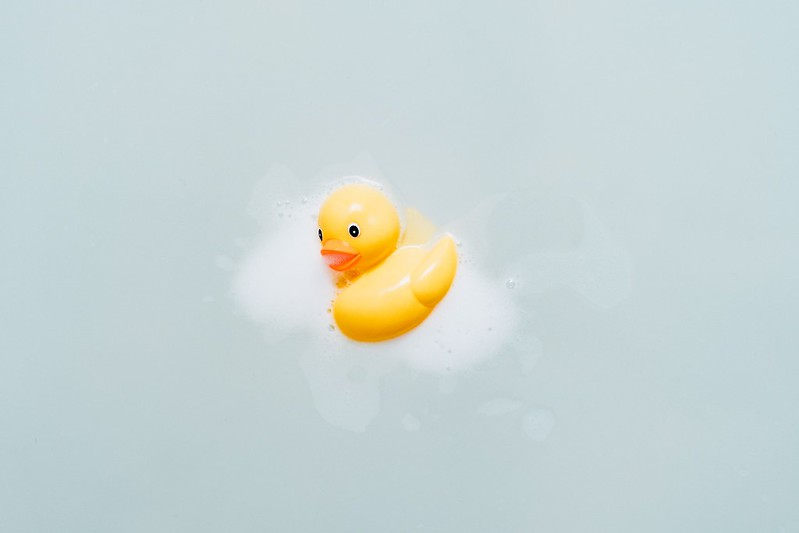 Yellow rubber duck with soapy foam on it.