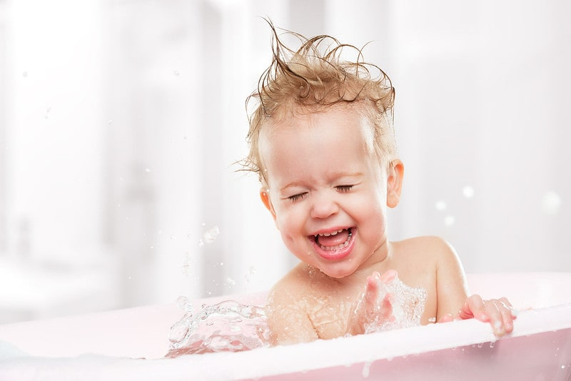 Happy baby laughing in the bath tub, bubbles splashing everywhere.