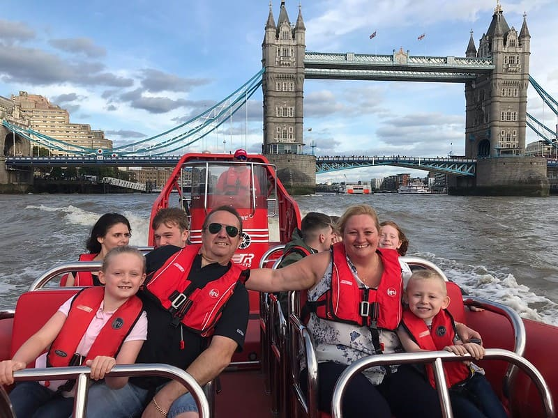A family enjoying a ride on the Thames Rockets' speedboat with Tower Bridge in the background.