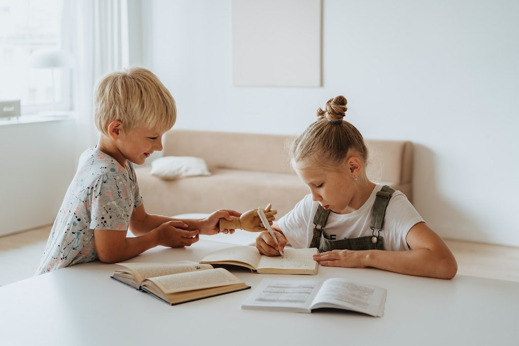 Little girl and boy sat at the table writing about Roman inventions in their notebooks.