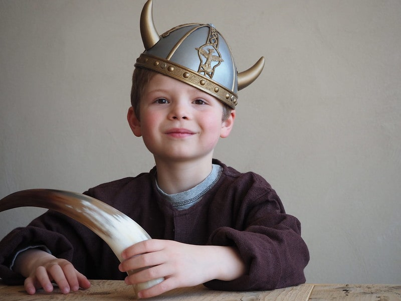 Young boy sat at a wooden table wearing a Viking helmet and holding a horn.