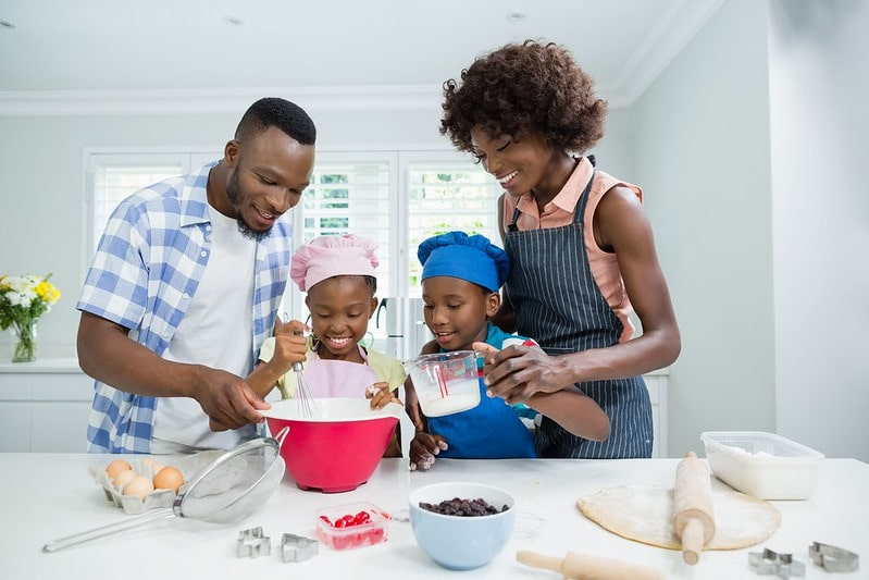 Parents and their two children in the kitchen baking a football cake together.