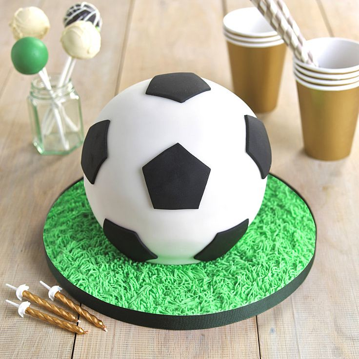 Cake shaped and decorated like a football, served on a board of green icing resembling grass.
