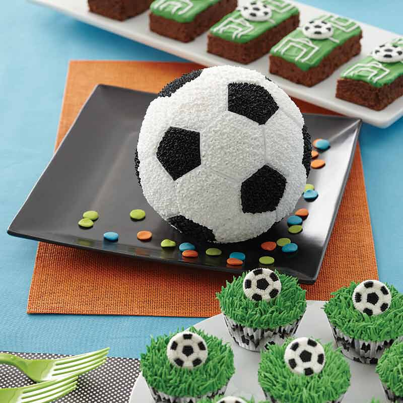 A football cake on a plate, some cupcakes decorated with green grass icing and an icing football and brownies iced to look like a football pitch.