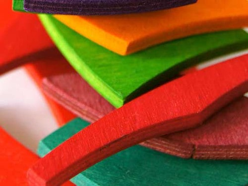 A pile of colourful wooden pieces cut out in different shapes.