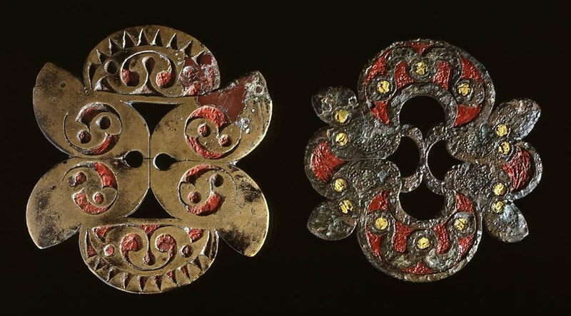 Two metal brooches from the Iron Age, showing off detailed metal work.