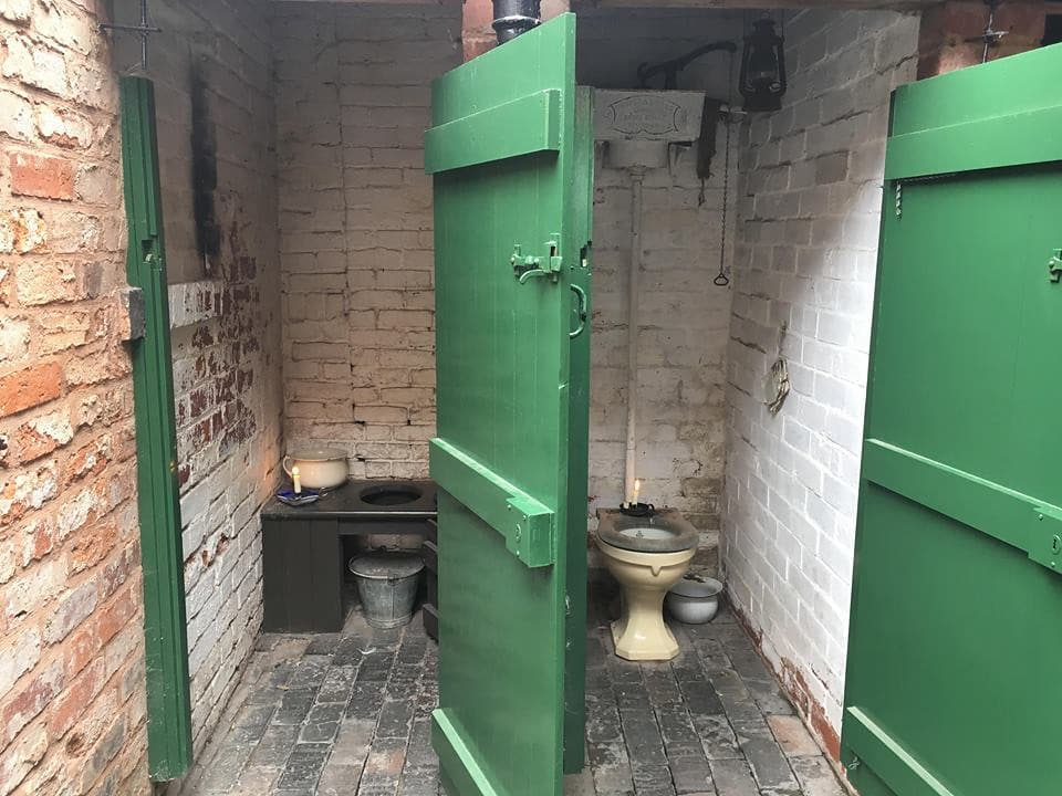 Victorian toilet cubicles with stone walls and green doors.