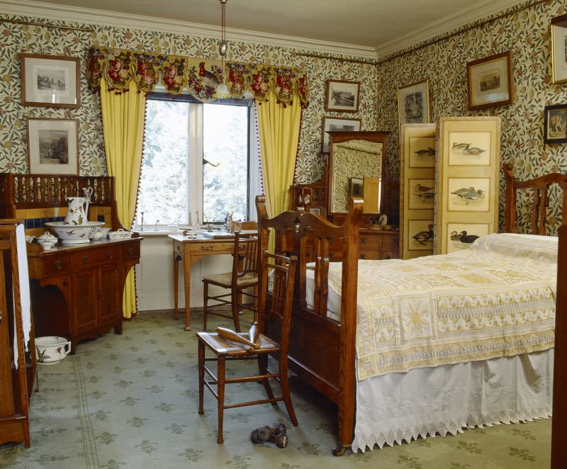 An upper-class Victorian bedroom with floral wallpaper and pictures on the walls.