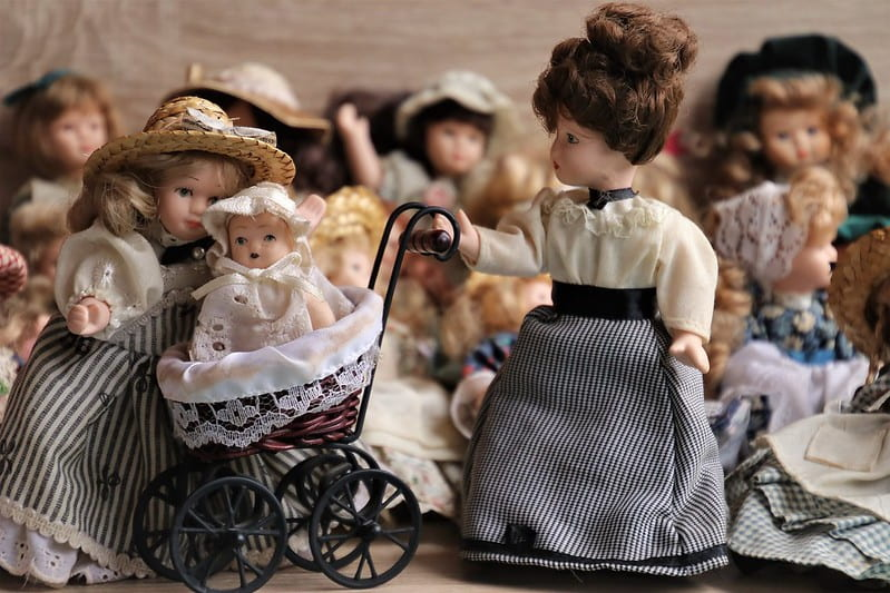 Dolls in dress from the Victorian era, one doll pushing a Victorian pram.