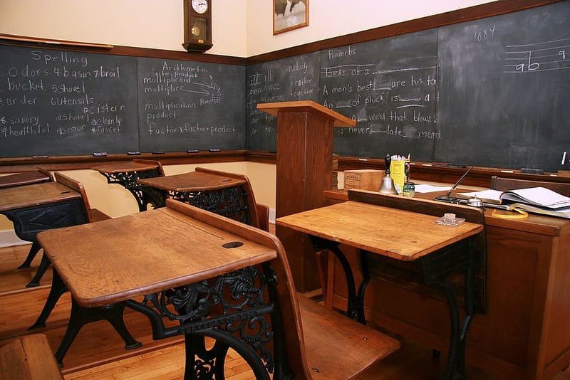 Victorian-era schoolroom with wooden desks and a blackboard.