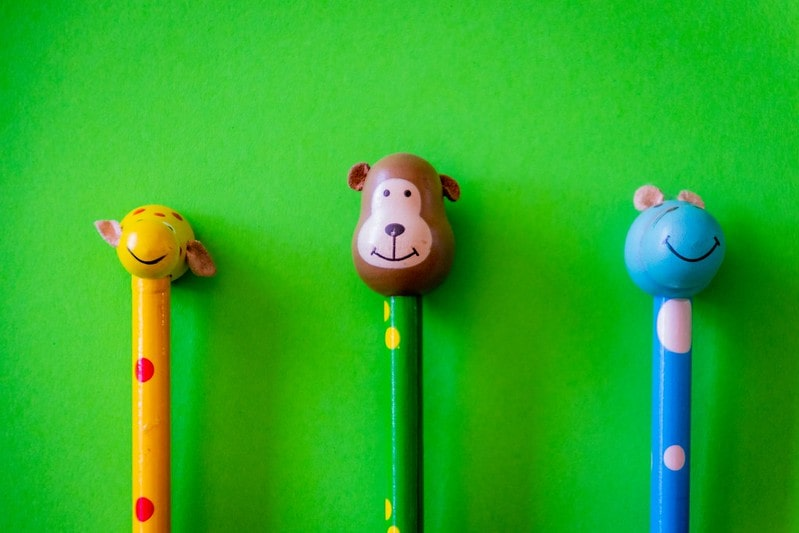 Three pencils with animal head figurines on the top (a giraffe, a monkey and a mouse).