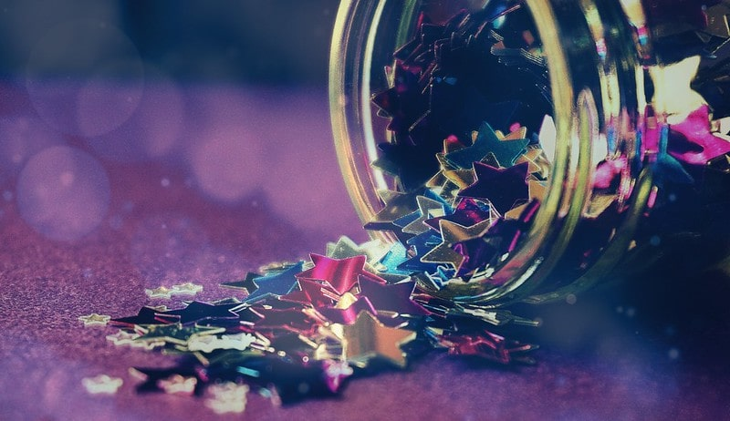 Coloured, shiny star sequins tipping out of a jar onto a surface.