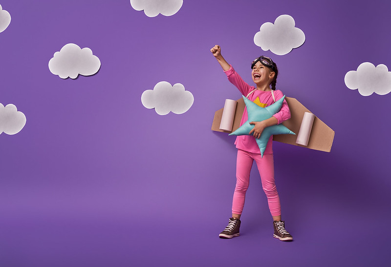 Little girl wearing a homemade astronaut costume with cardboard wings pretending to soar into the sky.