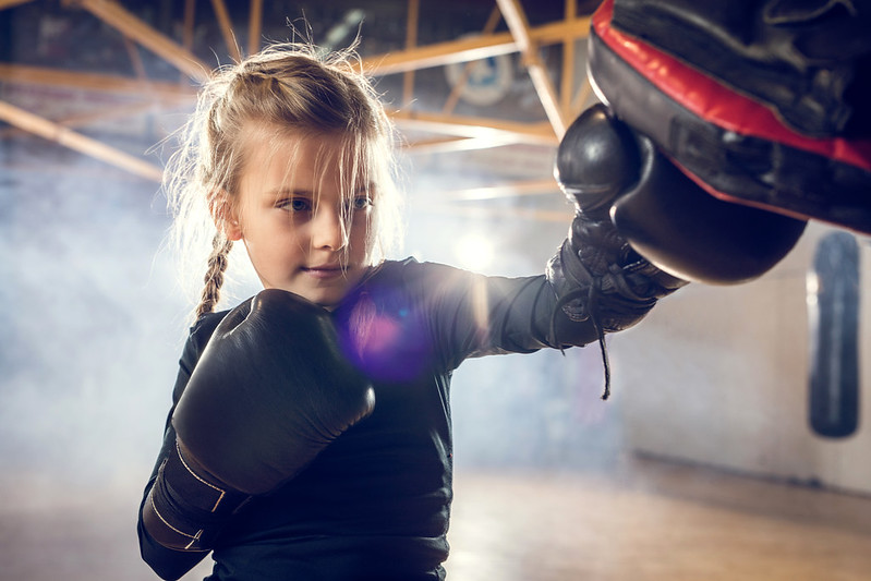 Young girl undergoing boxing training in black gloves