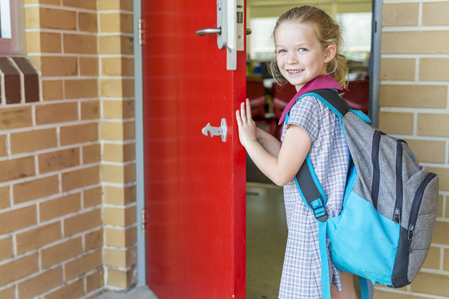 girl opening school door on first day at school