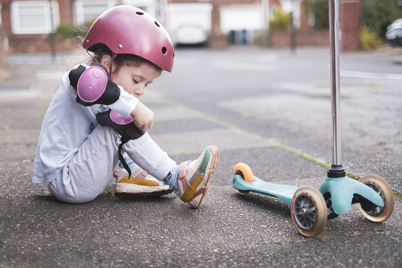 A little girl is putting on kneepads before going on her scooter.