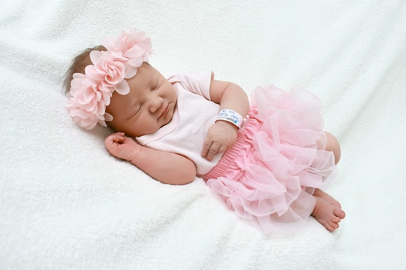 Baby girl wearing a pink tutu and matching flower crown, lying on a white blanket fast asleep.