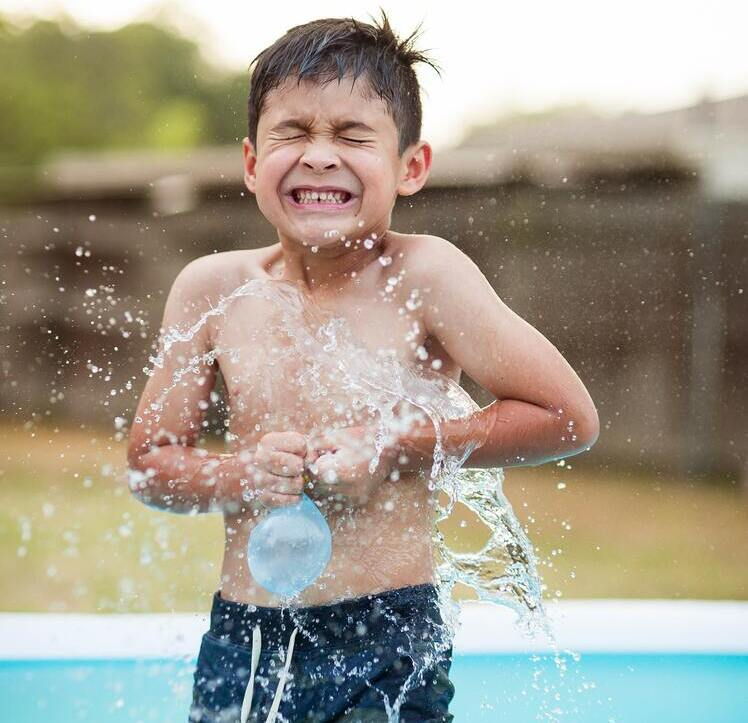 Young boy in a paddling pool in the garden getting splashed by a bursting water balloon.