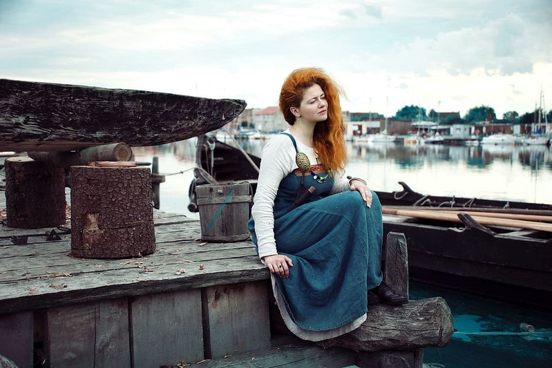 Woman sat by a Viking boat next to the water, wearing Viking clothing.