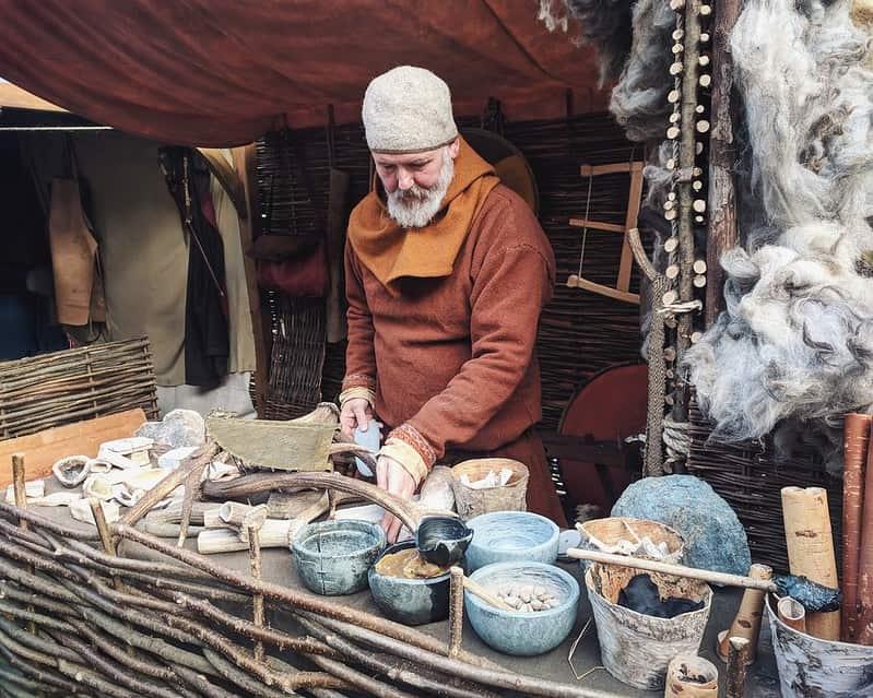 Man wearing Viking clothing, standing behind a stall making Viking pots and horns.