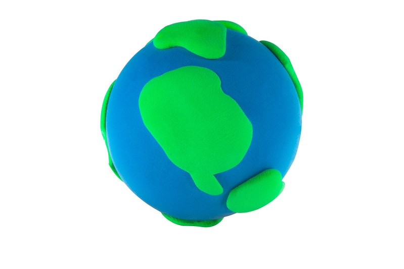 Plasticine model of planet Earth against a white background.