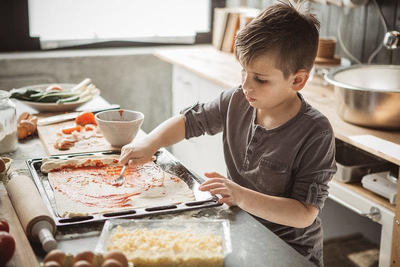 Young boy in the kitchen making homemade pizza.