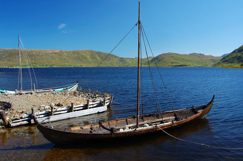 A Viking longship on water surrounded by hills and with a blue sky.